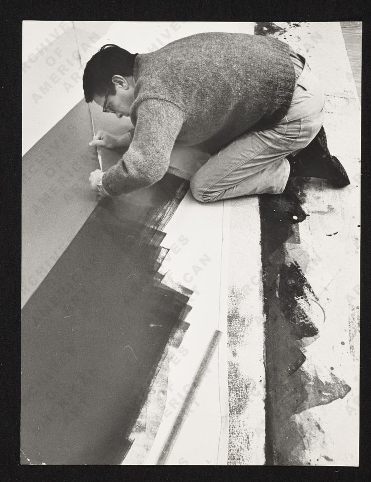 Noland painting on the floor of his studio, 1968