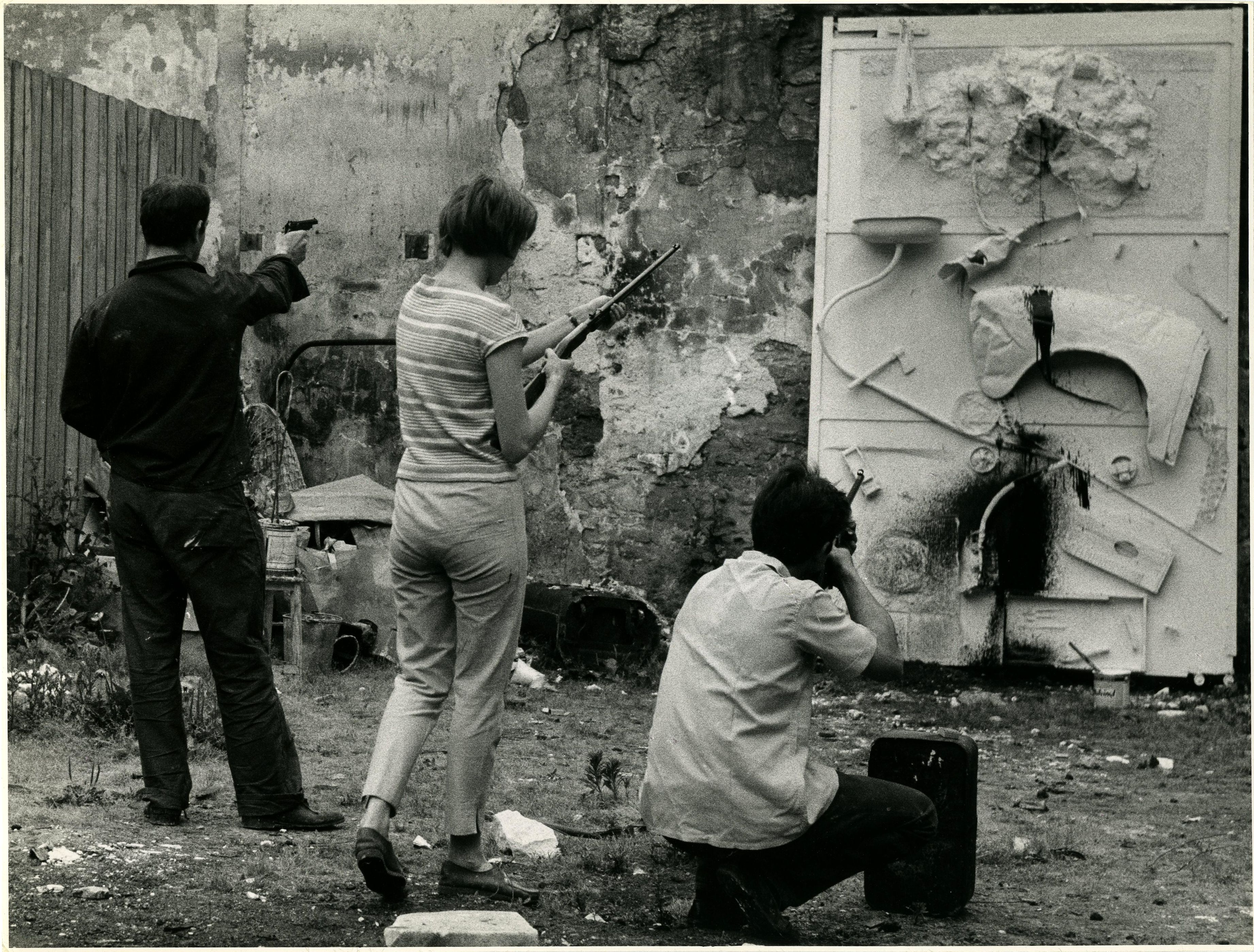 Jean Tinguely (far left) Niki and unidentified man, shooting paint at a nearly finished work, 1961 [photo: Shunk-Kender; © 2008 Niki Charitable Art Foundation, all rights reserved / VG Bild-Kunst Bonn 2012; photo © Roy Lichtenstein Foundation, Shunk-Kender]
