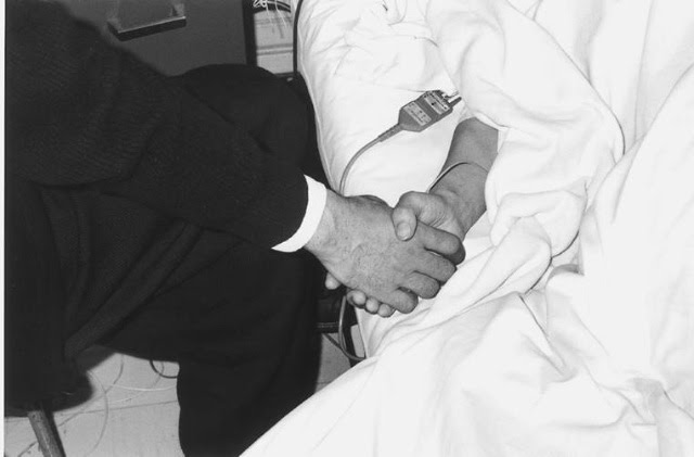 "Nobuyoshi holds Yoko's hand as she lay dying of ovarian cancer, 1971. The image was included in his ""Sentimental Journey"" photographic project that same year."