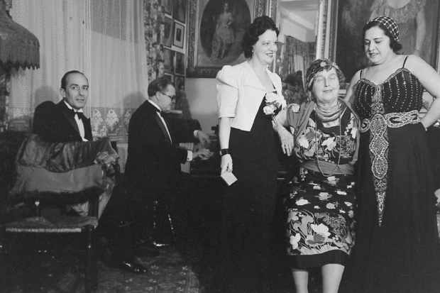 Florence, center of the group of three women, during a moment of intense drama during one of her performances at her home. Cosmé McMoon, is seen on the far left, others are unidentified