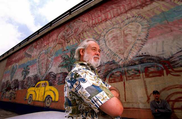 Muralist Frank Romero next to his mural on the 101 Freeway wall near Alameda on 05/02/2001. It was tagged with graffiti and then the lower third sprayed gray by Cal Trans which has a strict policy of removing graffiti. He intends to restore the piece and has been working on it a little at a time.