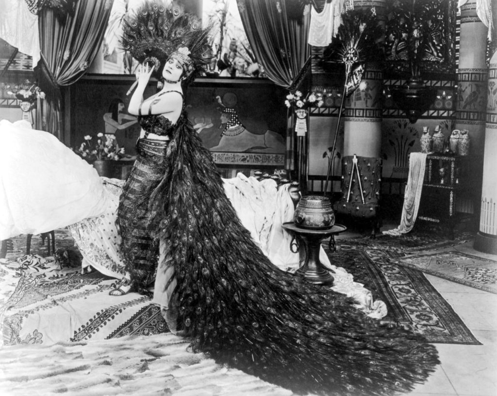 1917: American actor Theda Bara (1885 - 1955) holds a peacock feather fan next to a bed in a still from director J Gordon Edwards' film 'Cleopatra'. Bara is wearing a costume consisting of a bustier and sarong with a long peacock feather train and a peacock feather headdress.