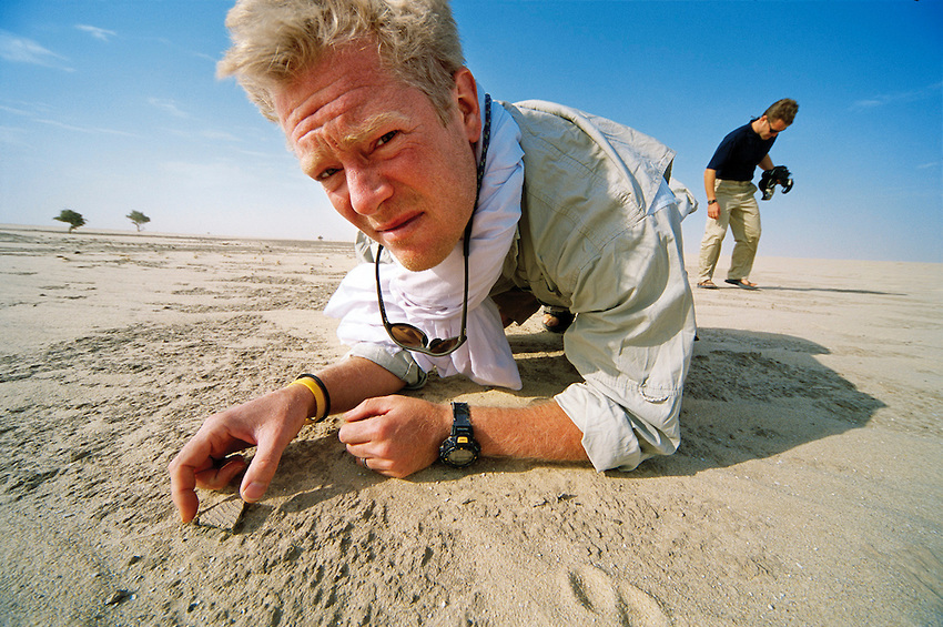 Geneticist Spencer Wells examines pottery in the Sahara - photo by David Evans