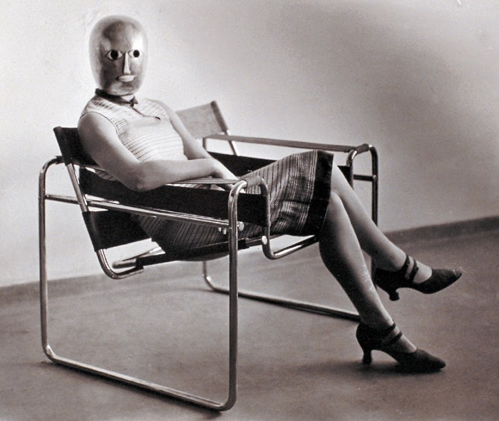 A Bauhaus group effort: Woman in B3 club chair by Marcel Breuer, wearing a mask by Oskar Schlemmer and a dress in fabric designed by Lis Beyer, 1926. Photograph by Erich Consemüller.